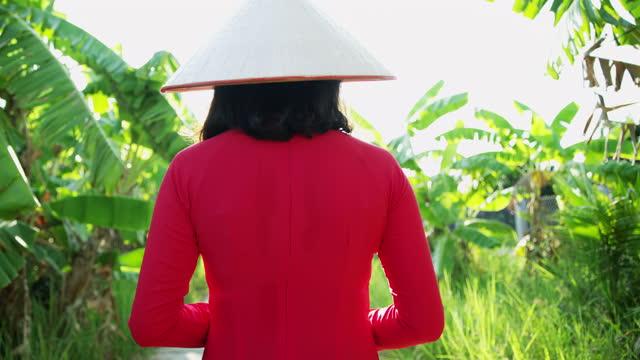 traditional vietnamese lady on mekong delta plantation vietnam - 赤のドレス点の映像素材/bロール