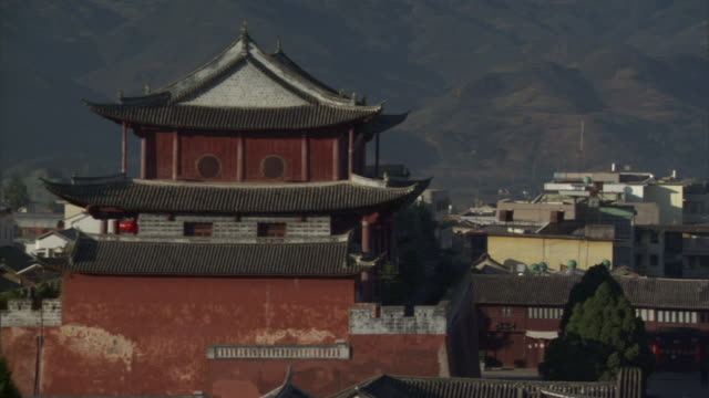 ws ha traditional weishan temple and roof tops with mount weibao in background, weishan, yunnan, china - 寶塔 個影片檔及 b 捲影像