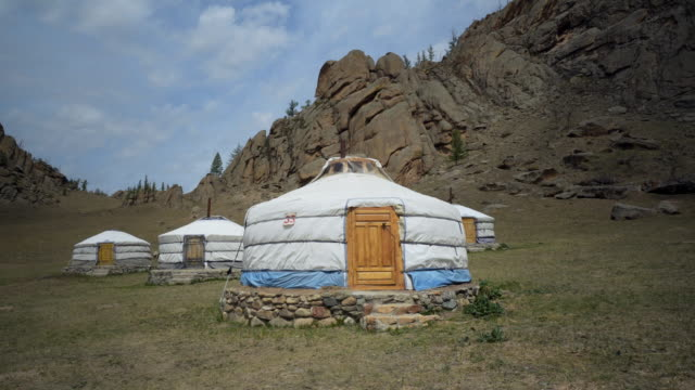 traditional white yurts on land by rocky mountains during sunny day - ulaanbaatar, mongolia - independent mongolia stock videos & royalty-free footage