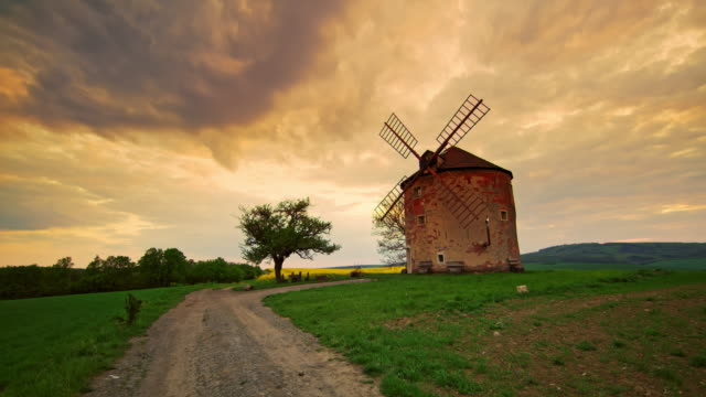 ds traditionelle windmühle bei sonnenuntergang - schotterstrecke stock-videos und b-roll-filmmaterial