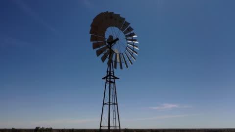 traditional windmill on farm with blue sky, australia, aerial view - propeller bildbanksvideor och videomaterial från bakom kulisserna