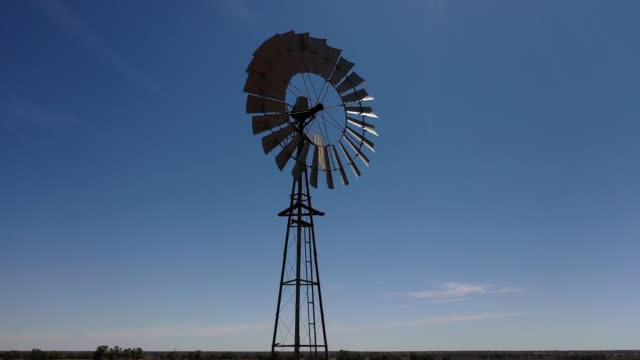 traditional windmill on farm with blue sky, australia, aerial view - propeller stock videos & royalty-free footage