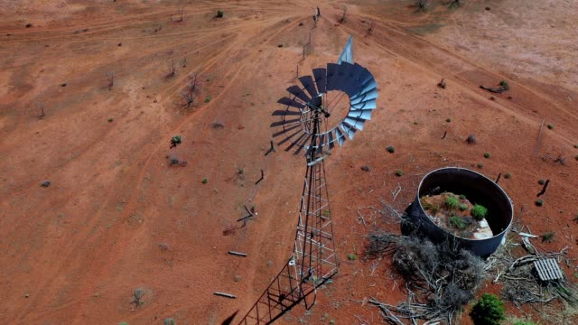 traditional windmill, water windpump on farm with dry red dirt field, australia, aerial view - bush stock videos & royalty-free footage