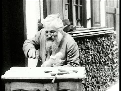 traditional woodcarver with long beard and spectacles carving figurine on workbench outside shop bearded man carving wooden statue on january 01 1910... - 1910 stock-videos und b-roll-filmmaterial