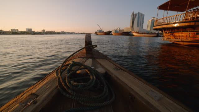 pov- traditional wooden dhow boat at sunset - dubai - nautical vessel stock videos & royalty-free footage