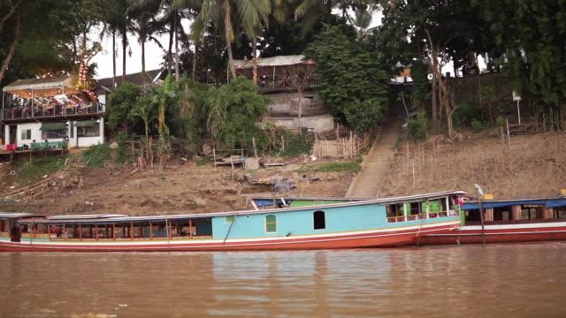 vidéos et rushes de croisière traditionnelle en bateau fluvial en bois sur le fleuve mékong au coucher du soleil - terre en vue
