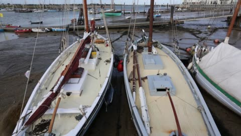 traditional wooden smack fishing boats beached in brightlingsea, essex, united kingdom on september 3, 2015. - sailing boat stock videos & royalty-free footage