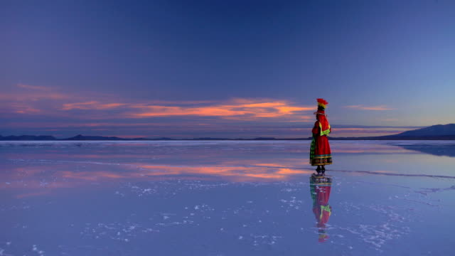 traditionally dressed female at sunset on bolivian landscape - ウユニ塩湖点の映像素材/bロール