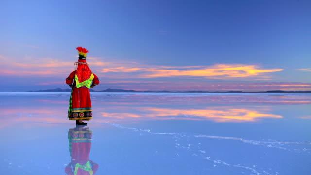 traditionally dressed female on bolivian salar de uyuni - ウユニ塩湖点の映像素材/bロール