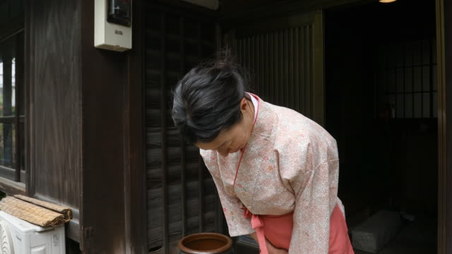 vídeos de stock e filmes b-roll de traditionally dressed japanese woman bowing to visitors to her inn - tradição