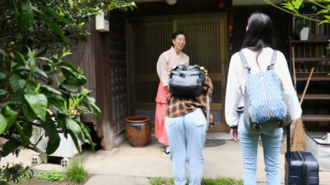 traditionally dressed japanese woman bowing to visitors to her inn - social grace stock videos & royalty-free footage