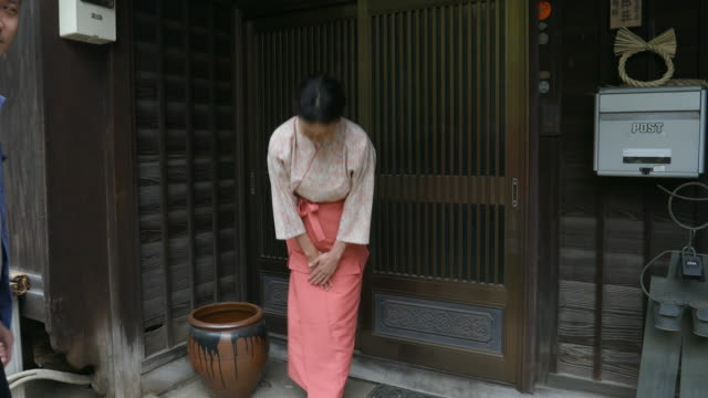 Traditionally Dressed Japanese Woman Bowing to Visitors to her Inn