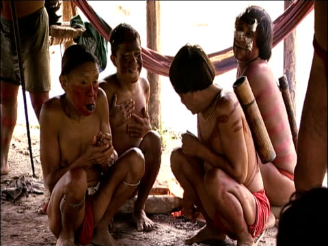 stockvideo's en b-roll-footage met traditionally dressed sanema villagers assemble in communal hut as shaman ceremony begins with aid of sakona hallucinogen south venezuelan rainforest - latijns amerikaanse cultuur