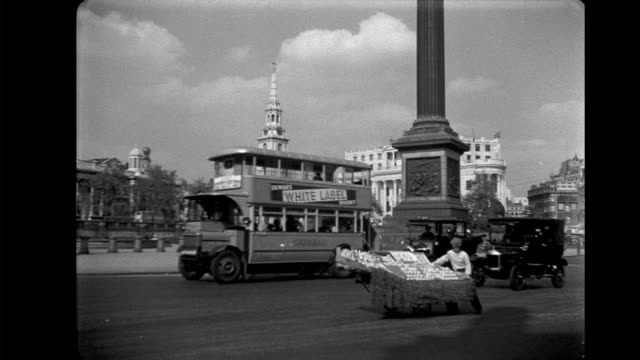 trafalgar square - base of nelson's column, st martin-in-the-fields, national gallery, south africa house, man with fruit cart / buses and cars... - 1930 video stock e b–roll