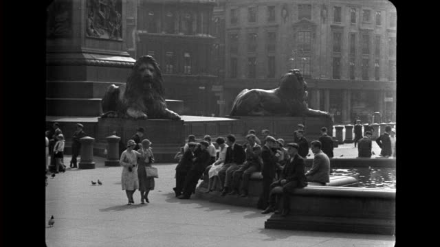 Trafalgar Square base of Nelson's Column with lion statues crowed with people / Buses and cars passing by Trafalgar Square on January 01 1936 in...