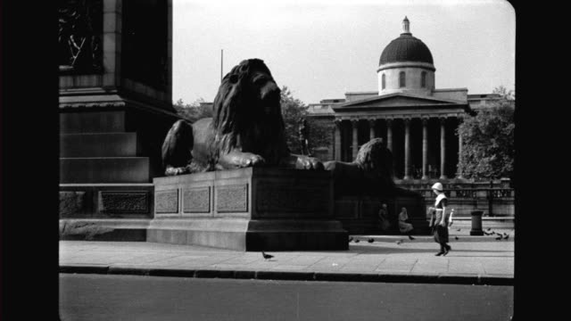 trafalgar square base of nelson's column with lion statues national gallery pedestrians cars and buses passing by trafalgar square on january 01 1936... - nelson's column stock videos and b-roll footage