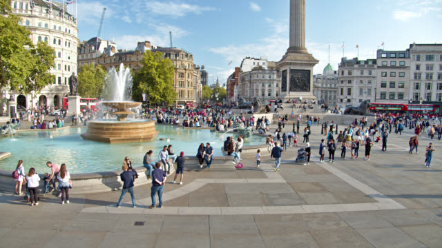 trafalgar square. london city. fountain. people. tourist. travel destination. in background red bus. big ben - editorial stock videos & royalty-free footage