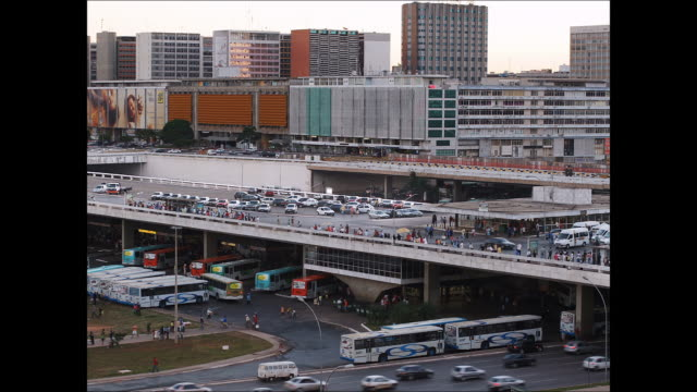 traffic and buses move around a busy bus station and shopping mall in brasilia, brazil. - brasilia stock videos and b-roll footage