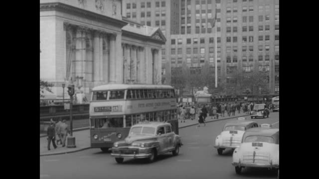 1948 nyc - traffic and commuters pass the nyc public library - 1948 stock-videos und b-roll-filmmaterial