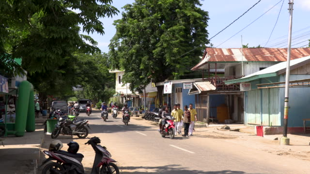 ws traffic and houses on street in city, labuan bajo, flores island, east nusa tenggara, indonesia - フロレス点の映像素材/bロール