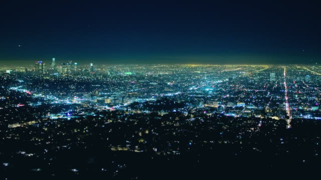 t/l ha ws traffic and lights moving across los angeles basin at night with view of downtown skyline / los angeles, california, usa  - distant stock videos and b-roll footage