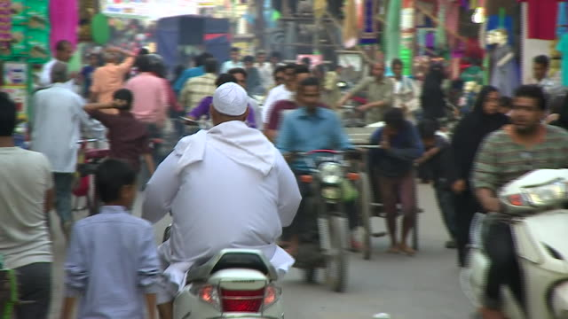 Traffic and muslim residents on the streets of Aligarh India a predominantly muslim city