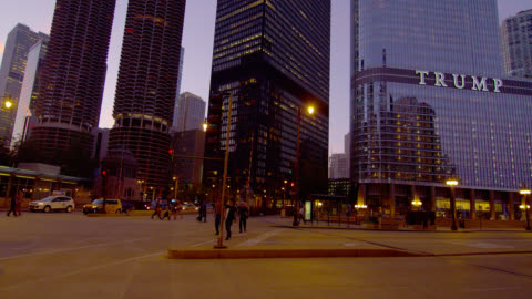 wide pan traffic and pedestrians at intersection to trump tower with wrigley building and tribune tower in background at dusk, chicago - wrigley building video stock e b–roll