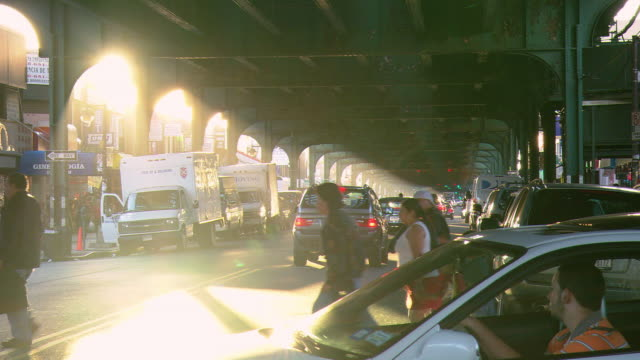 ws traffic and pedestrians beneath the elevated train overpass, with sunlight streaming through the arches / new york city, new york, united states - elevated train stock videos & royalty-free footage