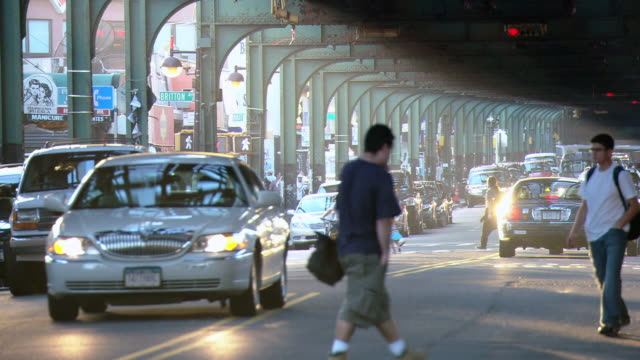 ms traffic and pedestrians beneath the elevated train overpass, with sunlight streaming through the arches / new york city, new york, united states - elevated train stock videos & royalty-free footage