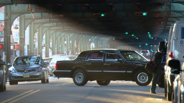 ms traffic and pedestrians beneath the elevated train overpass, with sunlight streaming through the arches and bicyclist passing parked cars / new york city, new york, united states - elevated train stock videos & royalty-free footage