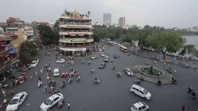 traffic and pedestrians cross a large intersection in hanoi. - hanoi stock videos and b-roll footage
