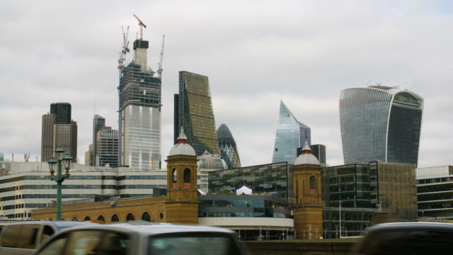traffic and pedestrians cross southwark bridge below views of the city of london skyline - sir norman foster building stock videos & royalty-free footage