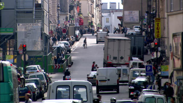 traffic and pedestrians crowd a busy street in paris. - population explosion video stock e b–roll