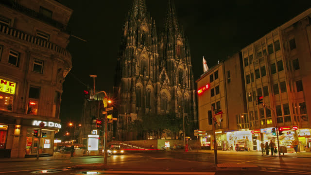 TIME LAPSE MEDIUM SHOT traffic and pedestrians in front of Cologne Cathedral at night, Cologne, Germany