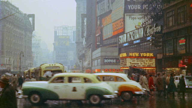 vídeos de stock, filmes e b-roll de 1953 ws traffic and pedestrians in rainy times square / new york city - 1950