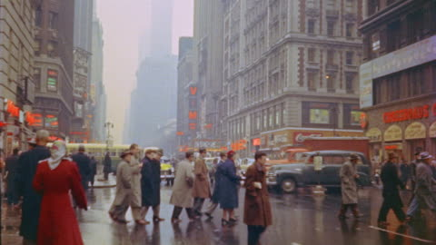 1953 montage traffic and pedestrians in rainy times square / new york city - 1950 stock videos & royalty-free footage