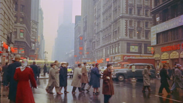 vídeos de stock, filmes e b-roll de 1953 montage traffic and pedestrians in rainy times square / new york city - 1950