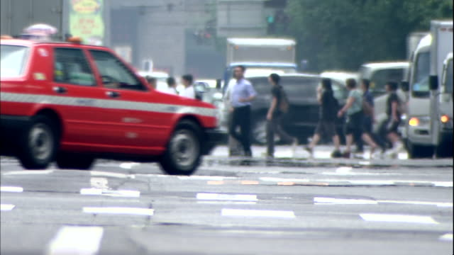 traffic and pedestrians maneuver through an intersection in tokyo, japan. - 熱波点の映像素材/bロール