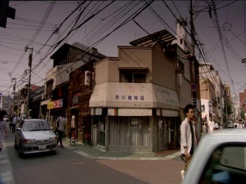 vídeos de stock, filmes e b-roll de traffic and pedestrians move along narrow street beneath jumbles of telegraph wires fukuoka - 1990 1999