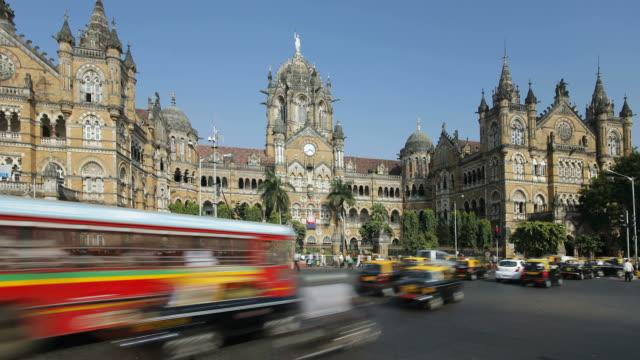 traffic and pedestrians move past the busy chhatrapati shivaji terminus train station in mumbai, india. - bahnhof stock-videos und b-roll-filmmaterial