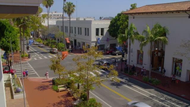 traffic and pedestrians move through an intersection on state street in santa barbara, california. - santa barbara bildbanksvideor och videomaterial från bakom kulisserna