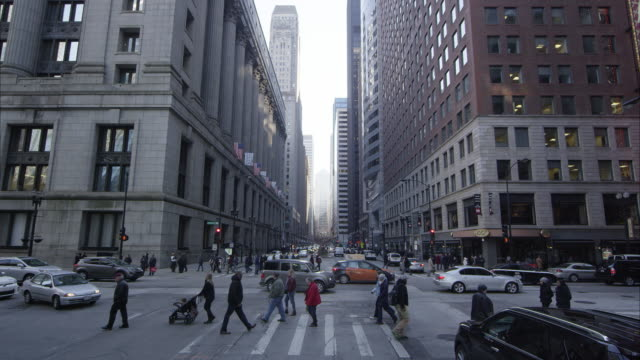 Traffic and pedestrians on a downtown Chicago intersection. Then camera tilts up to see buildings.