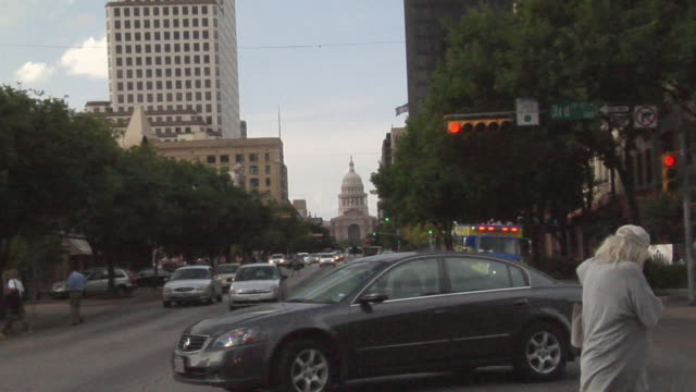 ws zi traffic and pedestrians on road leading to texas state capitol building/ austin, texas - texas state capitol building stock videos & royalty-free footage