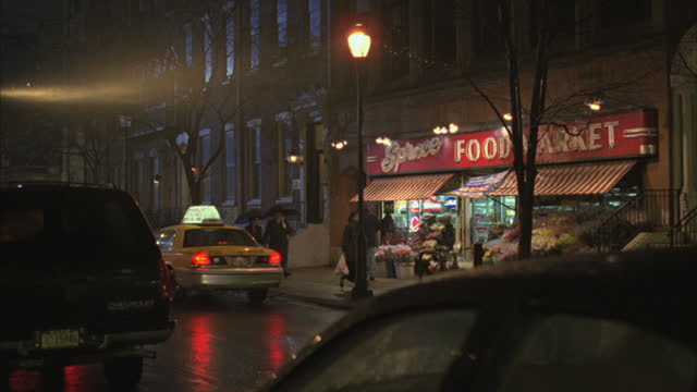traffic and pedestrians pass a food market in the rain. - western script stock videos & royalty-free footage