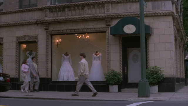 Traffic and pedestrians pass by the display window of a bridal shop.