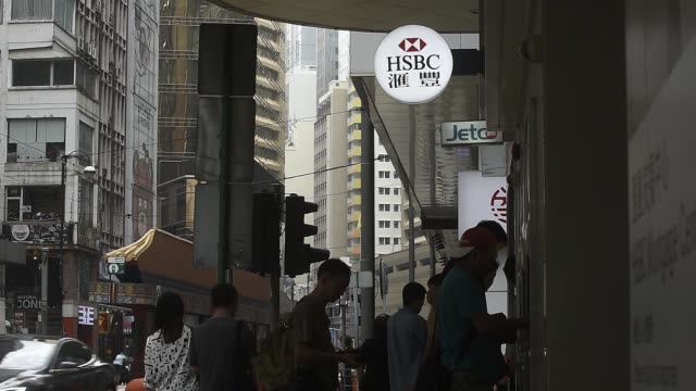 Traffic and pedestrians pass in front of an HSBC Holdings Plc bank branch in Hong Kong China on Saturday July 29 2017 Close up signage is displayed...