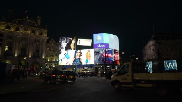 vídeos y material grabado en eventos de stock de traffic and pedestrians pass in front of the bright lights of piccadilly circus, london - señal comercial