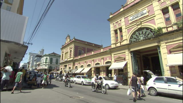 traffic and pedestrians pass storefronts in manaus, brazil. - manaus stock videos and b-roll footage