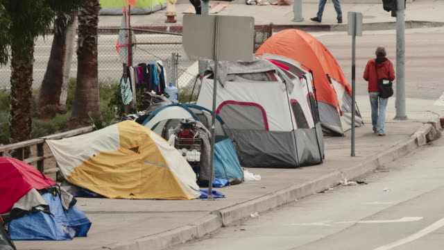 traffic and pedestrians pass the tents of homeless individuals lining a stretch of sidewalk in downtown los angeles - homelessness stock videos & royalty-free footage