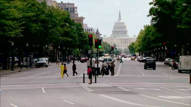 traffic and pedestrians pass the u.s. capitol building in washington, d.c. - pennsylvania avenue stock videos & royalty-free footage